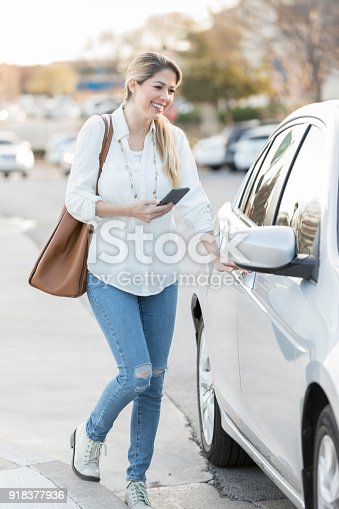 918377954 istock photo Woman uses mobile app to get ride in the city 918377936
