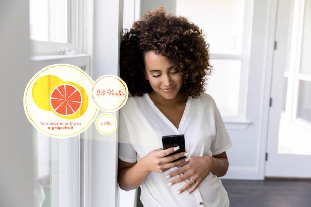 frau nutzt mobile app, um schwangerschaft zu verfolgen - wachstumstabelle baby stock-fotos und bilder
