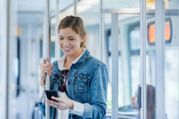 woman uses mobile app while riding commuter train - riding stock photos and pictures