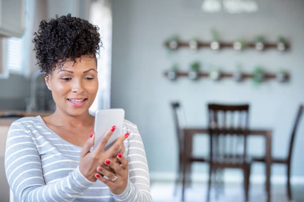 woman uses smart phone for virtual doctor's appointment from home - telemedicine stock pictures, royalty-free photos & images