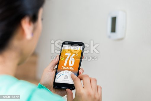 istock Woman uses smart phone to control thermostat 530816472