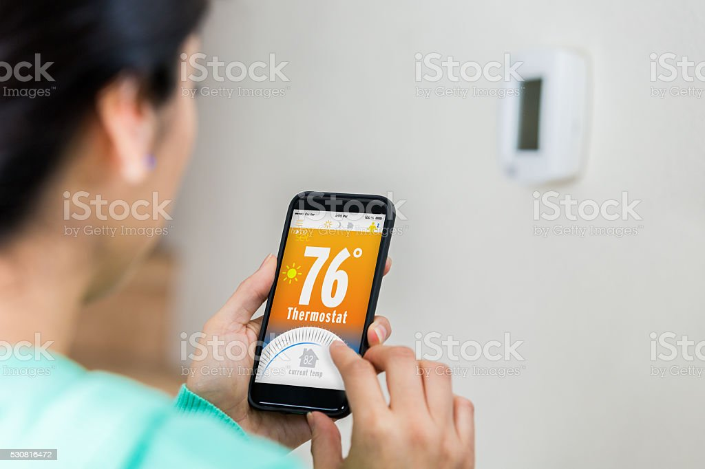 Woman uses smart phone to control thermostat stock photo