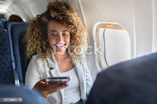istock Woman uses smartphone on airplane 1022880176