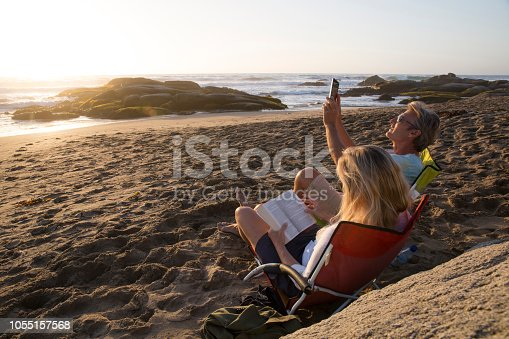 Mature woman uses tablet in beach chair as man photographs sunset, with digital tablet
