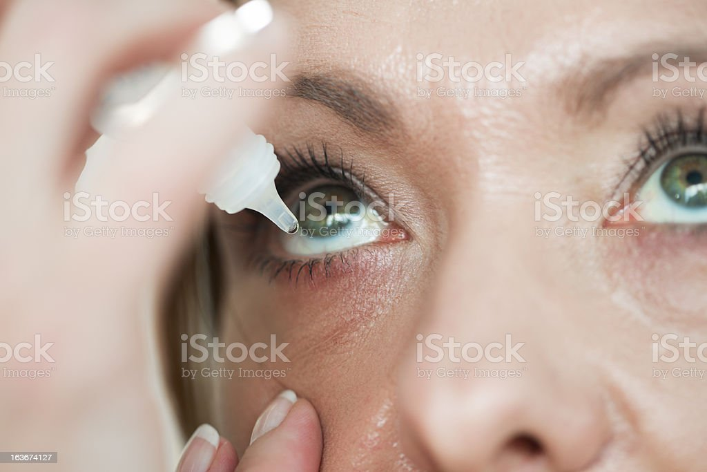 Woman usind eyedropper...applying eye drops stock photo