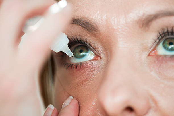 woman usind eyedropper...applying eye drops - dry stock pictures, royalty-free photos & images
