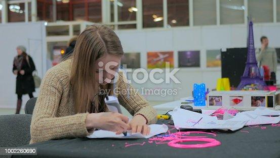 899701486 istock photo Woman using 3D printing pen 1002260690