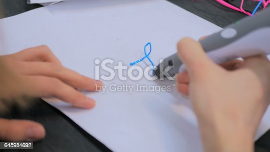 899701486 istock photo Woman using 3D printing pen 645984692