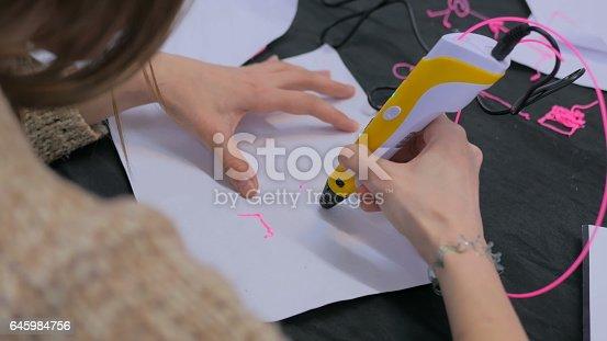 istock Woman using 3D printing pen 645984756