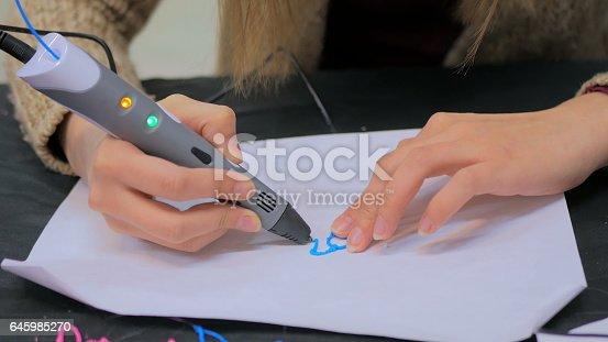istock Woman using 3D printing pen 645985270