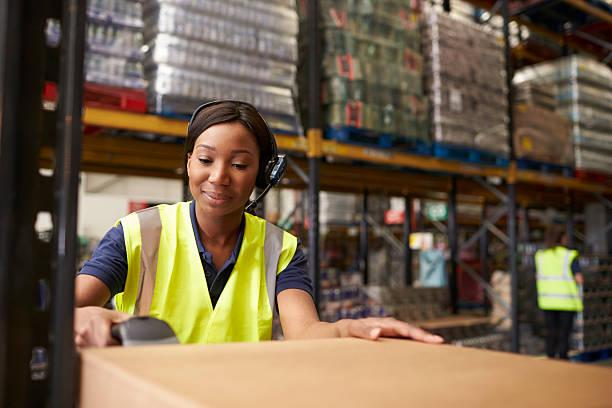 Mujer usando un lector de códigos de barras en un almacén de distribución - foto de stock