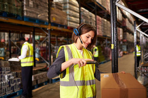 Woman Using A Barcode Reader In A Distribution Warehouse Stock Photo - Download Image Now