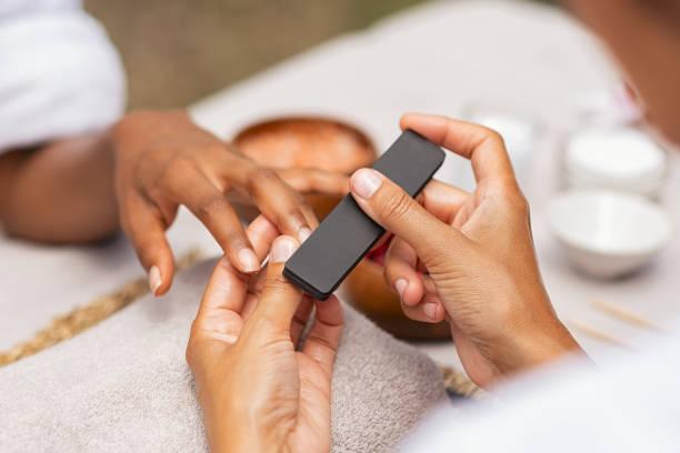 Femme utilisant un tampon pour classer l'ongle - Photo
