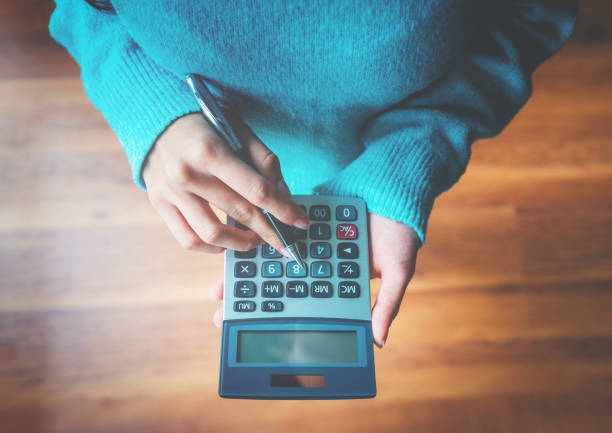 Woman using a calculator Finance, Savings, Wages, Loan, Calculator calculator stock pictures, royalty-free photos & images
