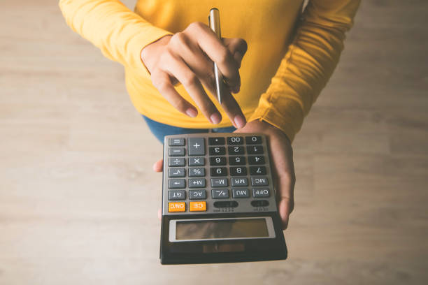Woman using a calculator with a pen in her hand Woman entrepreneur using a calculator with a pen in her hand, calculating financial expense at home office expense stock pictures, royalty-free photos & images