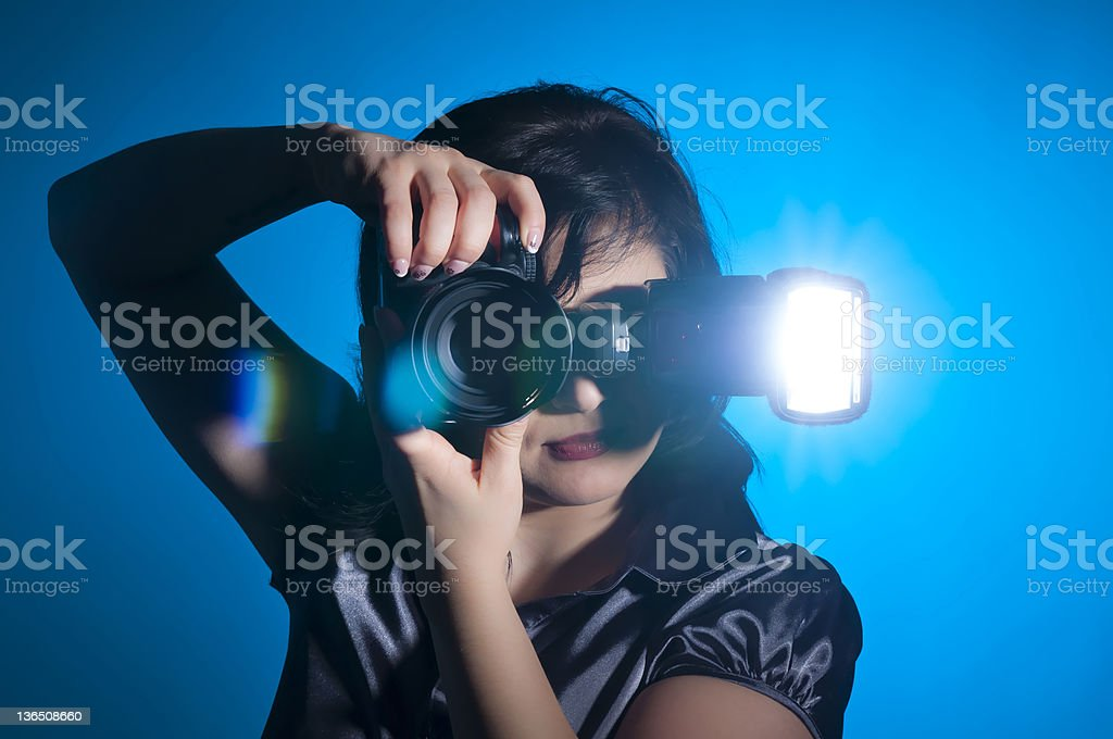 A woman using a camera to shoot a picture stock photo