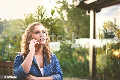 Beautiful woman in the nature, using her cell phone to talking