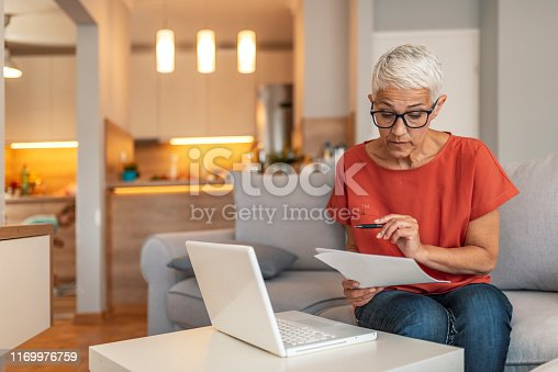 Serious aged woman in eyeglasses checking all bills, calculating expenses. Mature housewife sitting at table with laptop, looking through financial papers with focused expression. Serious woman focused on finding information on paper. Sitting at home in front of a laptop. The concept of business and online student learning.