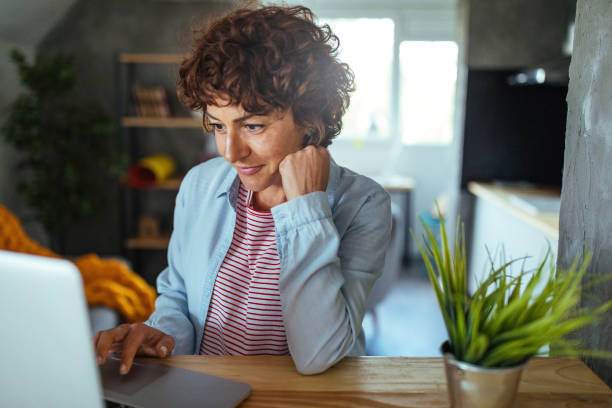 Woman using a computer Photo of mature woman working at home 40 44 years stock pictures, royalty-free photos & images