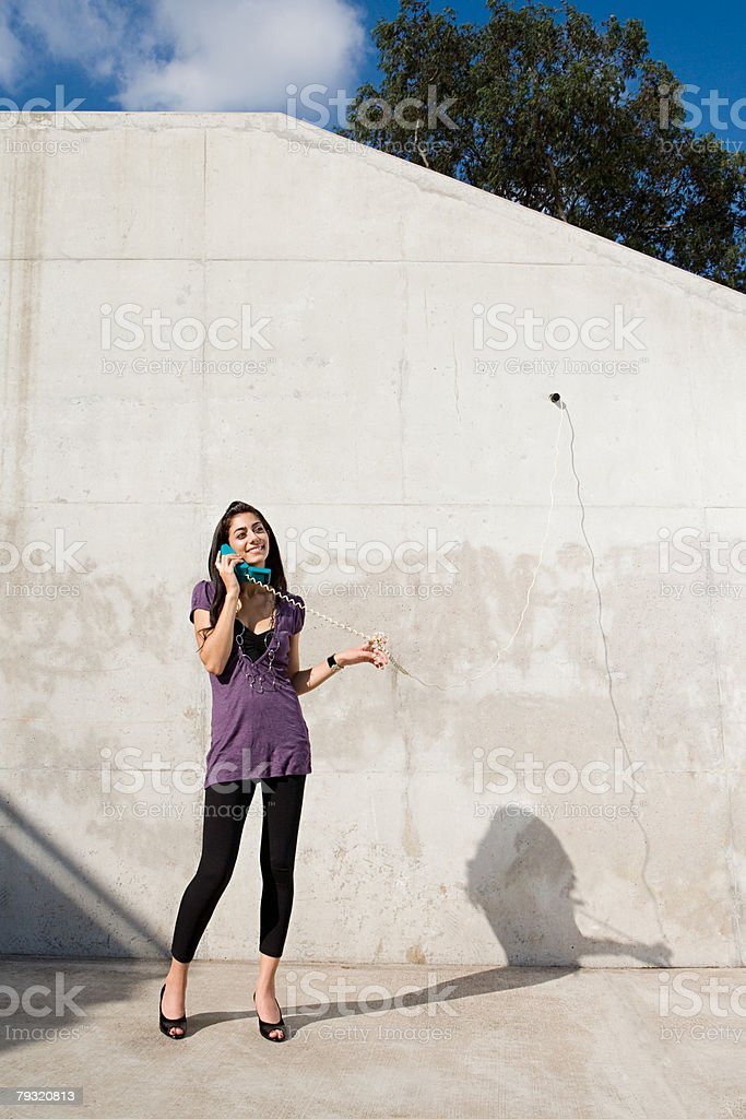Woman using a corded telephone outside 免版稅 stock photo