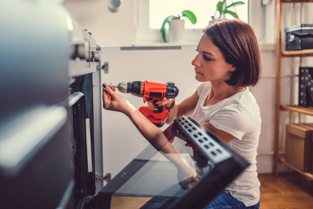 Woman using a cordless drill Woman working on a new kitchen installation and using a cordless drill diy stock pictures, royalty-free photos & images