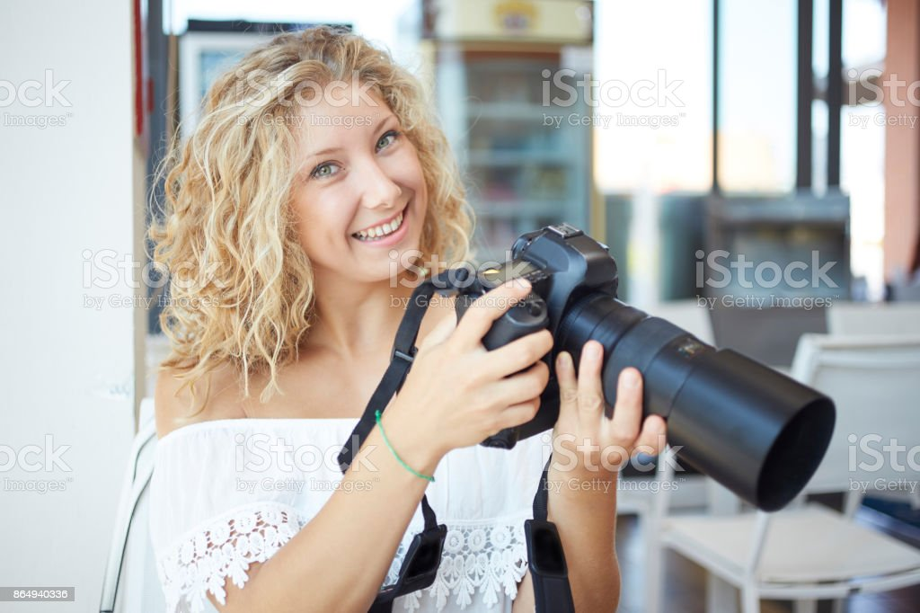 woman  using a digital reflex to take pictures and check on her laptop what she made stock photo