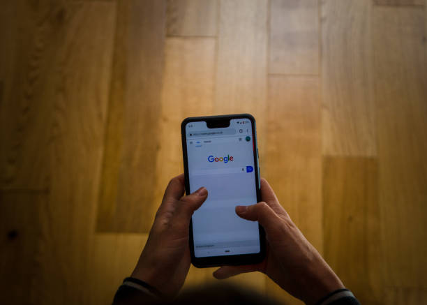 A woman using a Google Pixel 3 Xl  at home . A close up shot of a person using the google pixel phone in a canid scene against a clean background. google stock pictures, royalty-free photos & images