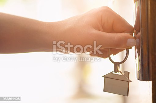 Woman using a house key on the front door. Close up of he woman's hand. She is turning the key in the lock. Back lit. The key ring has a house icon on it.