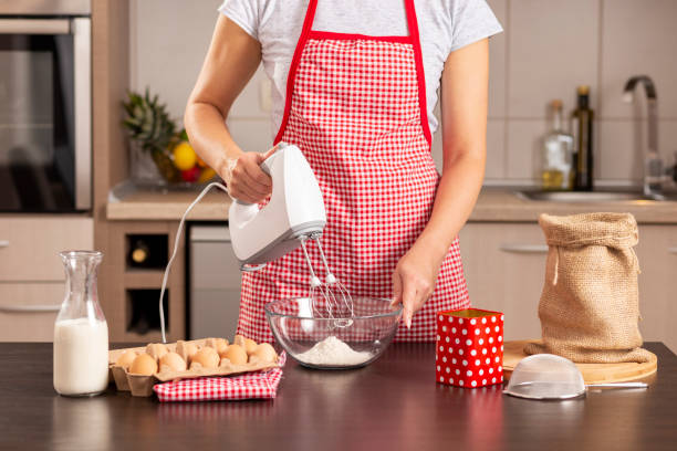 Woman using a kitchen mixer Detail of female hand holding mixer and mixing a pancake dough on the kitchen counter. Selective focus on the hand holding the bowl electric mixer stock pictures, royalty-free photos & images