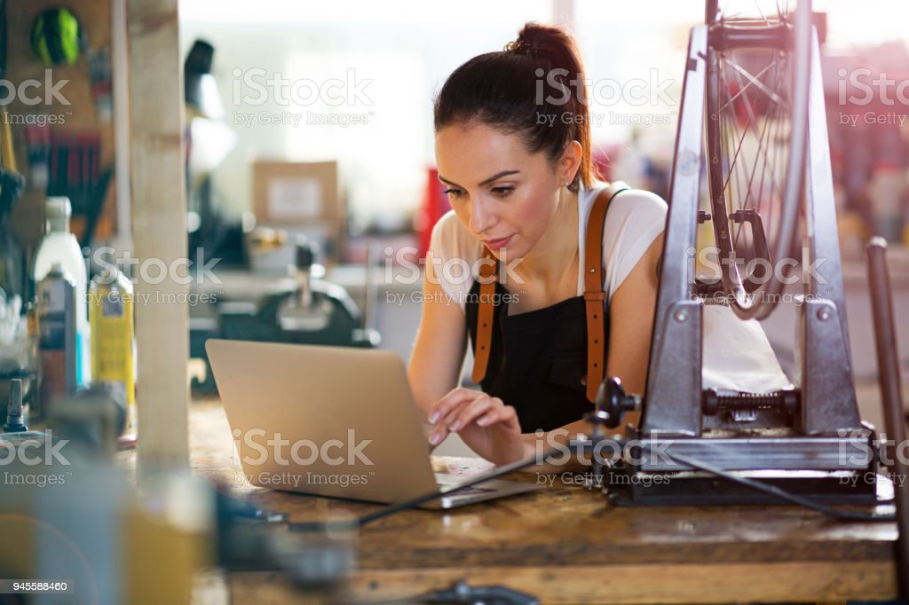 Woman using a laptop in a bicycle repair shop stock photo