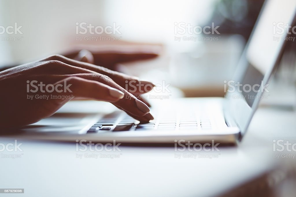 Woman using a laptop indoors, close up of hands Woman sitting at the desk and using a laptop in an office or at home, close up of hands, unrecognizable person. Dark tone. Adult Stock Photo