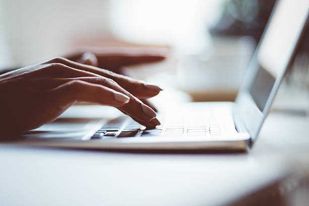 Woman using a laptop indoors, close up of hands stock photo