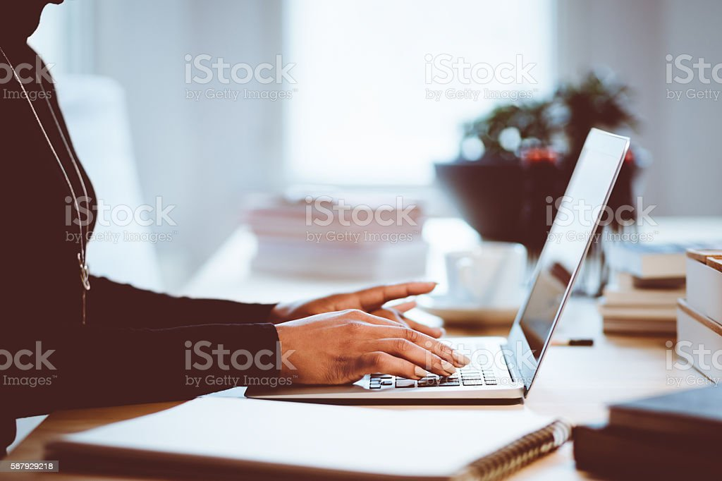 Woman using a laptop indoors, close up of hands Woman sitting at the desk and using a laptop in an office or at home, close up of hands, unrecognizable person. Adult Stock Photo