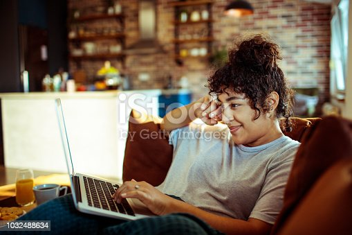 Close up of a young woman using a laptop at home