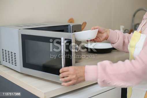 istock Woman using a microwave oven 1137517388