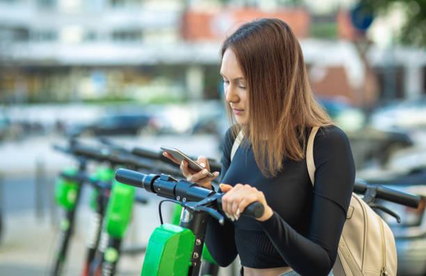 Eine Frau, die ein Handy zum Entsperren eines elektrischen Rollers per App – Foto