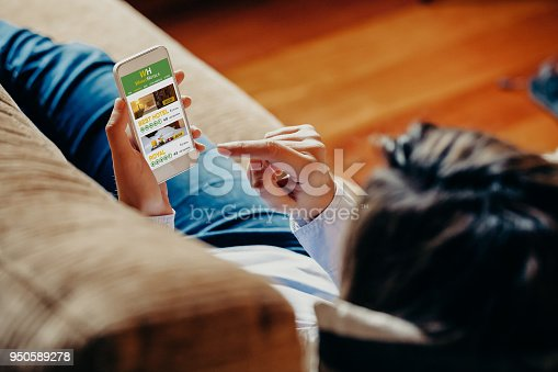istock Woman using a mobile phone to book hotel for vacation while rest on a sofa at home. 950589278