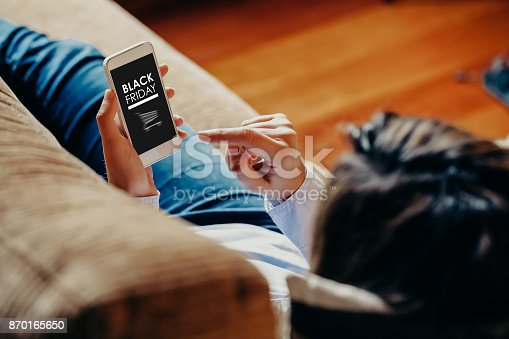 istock Woman using a mobile phone to buy at Black Friday special offers at home. 870165650