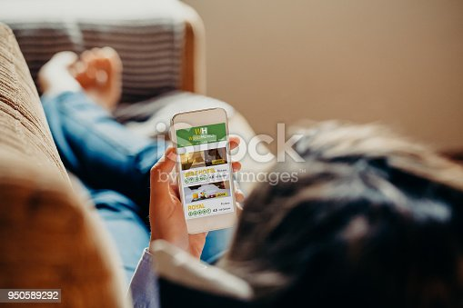 istock Woman using a mobile phone to search hotel for vacation while rest on a sofa at home. 950589292