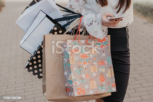 istock Woman using a mobile phone with shopping bags 1038158296