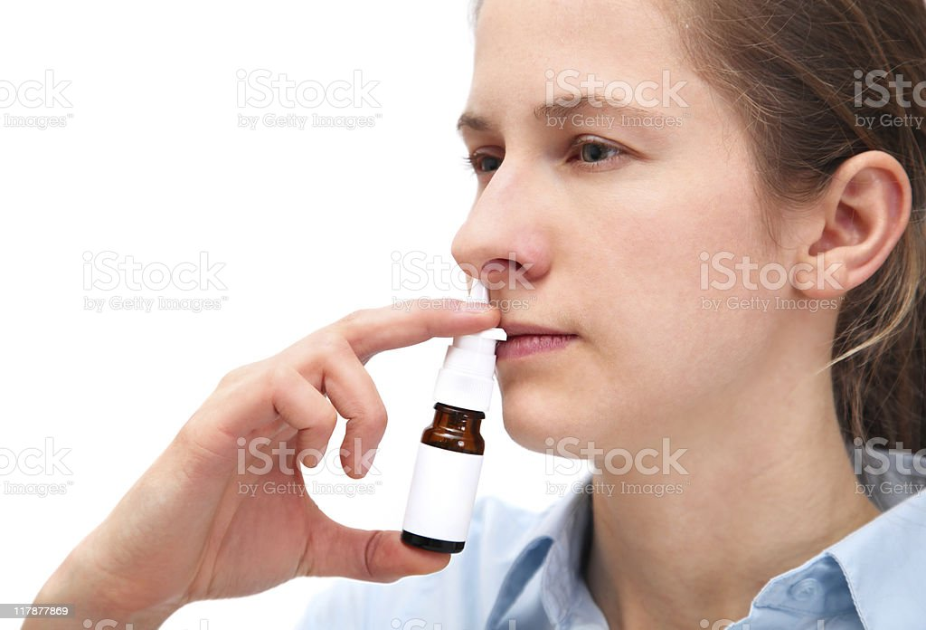 Woman using a nasal spray stock photo