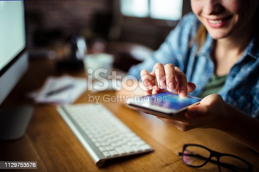 Close up of a young woman using a phone while working