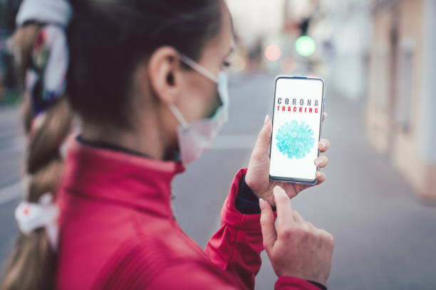 Woman using a phone with the coronavirus tracking app installed stock photo