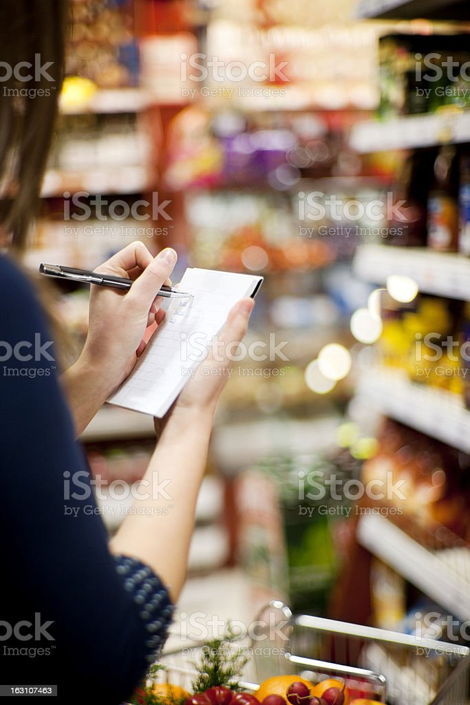 A woman using a piece of paper and pen in a store stock photo