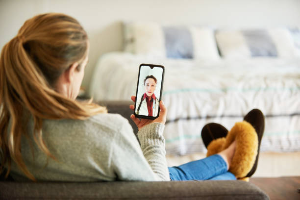 Woman using a smart phone app to talk with her doctor from home stock photo