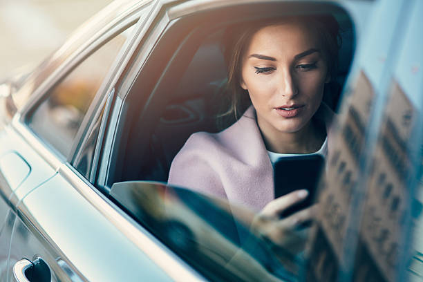 Woman using a smart phone in a car stock photo