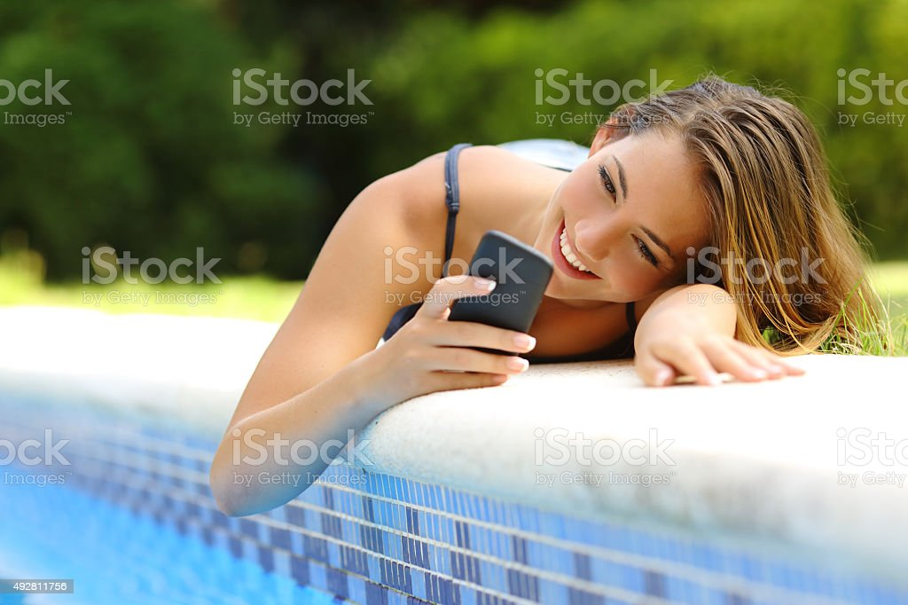 Woman using a smart phone in a poolside in summer stock photo