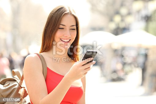 istock Woman using a smart phone in the street in summer 475177434