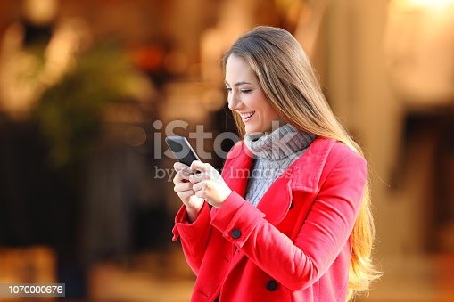 Happy woman using a smart phone in winter in a commercial centre in the street