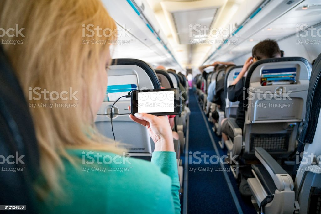 Woman using a Smart Phone on an Airplane stock photo